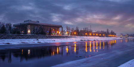 uzhhorod, ukraine - 26 DEC 2016: winter cityscape at dawn. beautiful scenery on the river uzh. city lights reflecting in the water. snow on the embankment Editorial