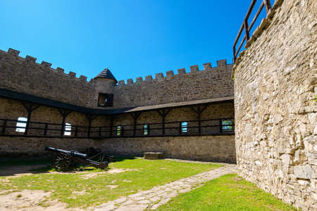 Stara Lubovna, Slovakia - 28 AUG 2016: ancient cannon in the inner courtyard of the castle. great stone walls of a fortrece. popular travel destination Editorial
