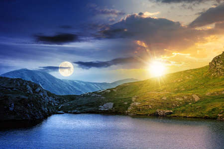 day and night time change concept above summer landscape with lake on high altitude. beautiful scenery of fagaras mountain ridge. open view in to the distant peak beneath a clouds with sun and moon Stock Photo