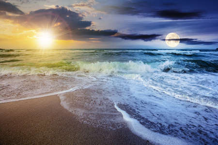day and night time change concept above sea tide on a cloudy twilight. green waves crashing golden sandy beach with sun and moon above the horizon. storm weather approaching. summer holiday concept