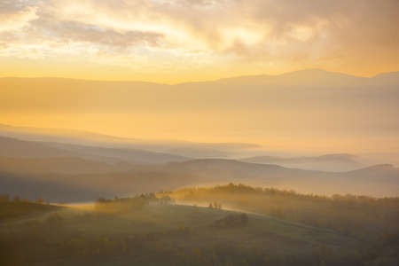 mountainous countryside landscape at foggy sunrise. wonderful autumnal nature scenery with distant rural valley in glowing mist. trees and fields on hills in morning light