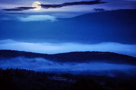 glowing fog in the rural valley at night. beautiful mountain landscape in full moon light. view from the hill