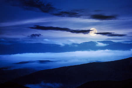rural landscape at night. mist in the distant valley in full moon light. silhouette of trees and hills Stock Photo
