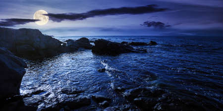 sea coast scenery at night. boulders in the calm water. few clouds on the sky in full moon light. lonely place for summer vacations. sunny weather