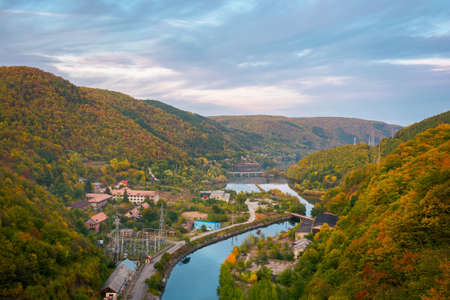 view from tarnita dam on the warm somes river. autumnal countryside landscape at sunset. trees in colorful foliage on the hill. apuseni mountains, cluj country, romania Stock Photo