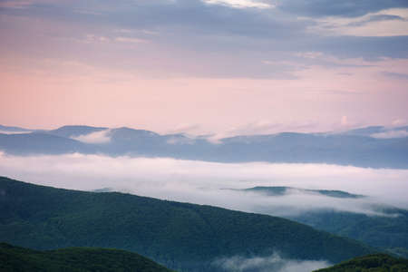 mountainous rural landscape at dawn. trees and agricultural fields on hills rolling in to the distant misty valley. ridge beneath a colorful sky in morning light