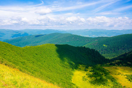 grass on the steep hill. view in to the distant valleys and Gorgany ridge beneath a blue sky with clouds. wonderful summer landscape on a sunny weather in carpathian mountains