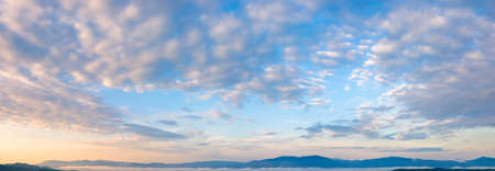 fluffy clouds on the azure sky at sunrise. beautiful nature background. panoramic view in golden morning light