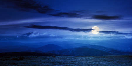 mountain meadow at night. beautiful landscape with clouds above horizon in full moon light. wonderful nature background