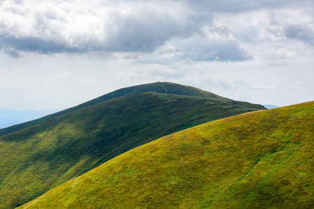 rolling hills an meadows of borzhava ridge. beautiful nature scenery with grassy slopes in dappled light. wonderful summer landscape of ukrainian carpathian mountains on a sunny day Stock Photo