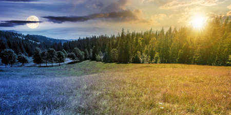 day and night time change concept of mountainous countryside panorama. trees on the meadow along the road. coniferous forest on the hills. abstract scenery with sun and moon on the sky in summer Stock Photo