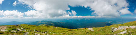 mountain panorama on a sunny day. beautiful nature background. gorgeous cloudscape above the mountain ridge with grassy meadows. travel back country concept