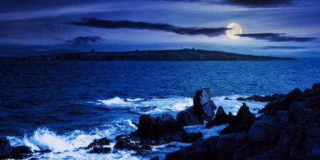 seascape at night. wonderful scenery with island and cliffs on the shore in full moon light. clouds above horizon. fantasy travel destination in summer Stock Photo