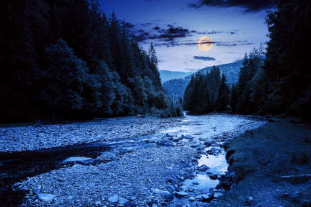 mountain river runs through forested valley. countryside scenery on a summer night. trees and stones on the shore in full moon light. low ammount of water. stream shallowing or drought concept Stock Photo