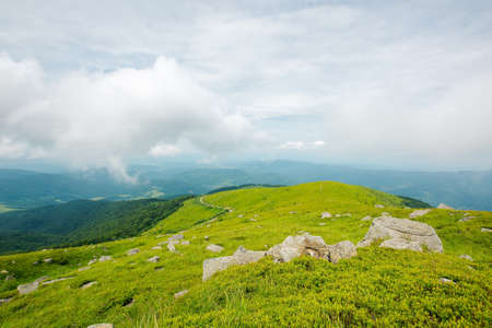 green nature landscape. beautiful summer scenery in mountains. stones on the grassy hills rolling in to the distant ridge beneath a cloudy sky