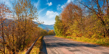 old country road in mountains. trees in colorful foliage in morning light along the serpentine curve. sunny weather with clouds on the sky above the distant range