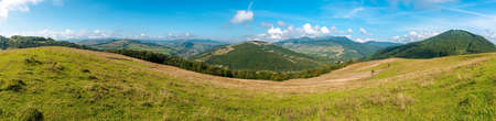 carpathian countryside in september. beautiful mountain landscape with grassy field on the hill. rural scenery with village in the distant valley on a sunny day with clouds on the sky Stock Photo