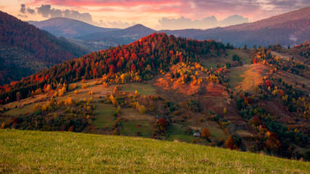 mountainous countryside at dusk. beautiful rural landscape with rolling hills and meadows. forest in colorful foliage. dramatic sky with glowing clouds