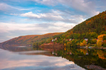 mountain lake somesul cald at sunset. beautiful autumnal countryside landscape of cluj country, romania. trees on the hill in colorful foliage and clouds on the sky reflecting on the water surface Stock Photo