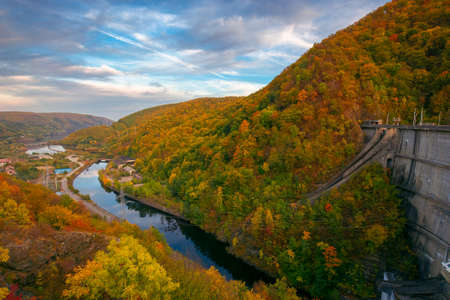 countryside scenery with river at sunset. beautiful mountain landscape of romania in autumn season. village in the valley. dramatic sky in evening light