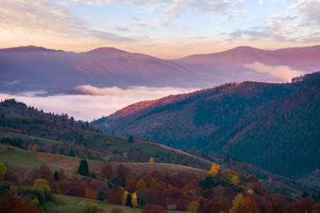 mountainous countryside in autumn at sunrise. beautiful scenery with rural fields on hills rolling in to the distant valley full of fog. clouds above the ridge in morning light