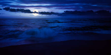 calm sea scenery at night. waves wash empty sandy beach in full moon light. relax and summer vacation concept. warm velvet season weather with clouds on the sky
