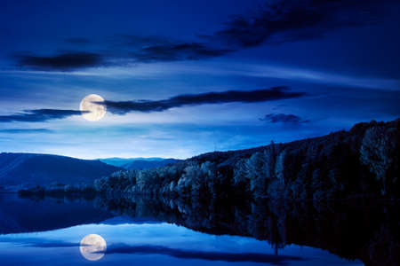 beautiful autumn landscape by the lake at night. forested mountains reflecting in the water surface in full moon light