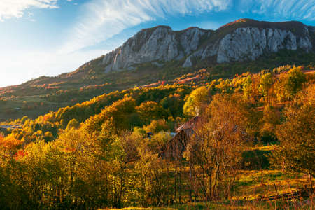 rocky formation in apuseni mountains at sunset. gorgeous autumn landscape in evening light. trees on the hills in colorful foliage. location masivul-vulcan, hunedoara country of romania Stock Photo