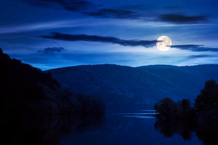 beautiful scenery with lake at night. dark clouds reflecting on the water surface. wonderful autumnal landscape in mountains in full moon light Stock Photo