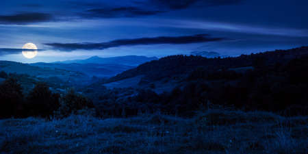mountainous countryside landscape at night. pastures and rural fields near the forest on the hills. beautiful early autumn nature scenery with clouds on the sky in full moon light Stock Photo