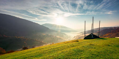 rural landscape at sunrise. beautiful autumnal mountain scenery. green grassy meadow on the hillside. fog down in the valley. sun and fluffy clouds above horizon