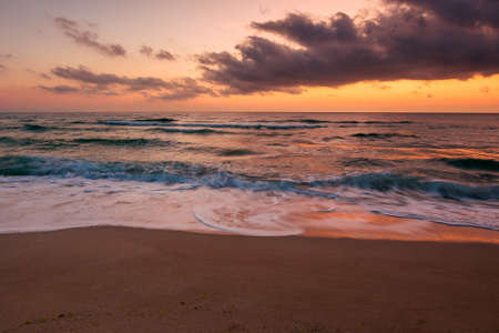 calm sea scenery at dawn. waves wash empty sandy beach at twilight. relax and summer vacation concept. warm velvet season weather with clouds on the sky
