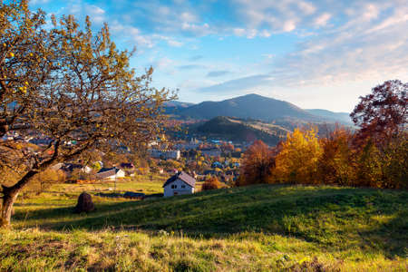 carpathian rural landscape in autumn. village in the valley at the foot of the mountain. beautiful countryside scenery in evening light. trees in fall foliage on the grassy hills Stock Photo