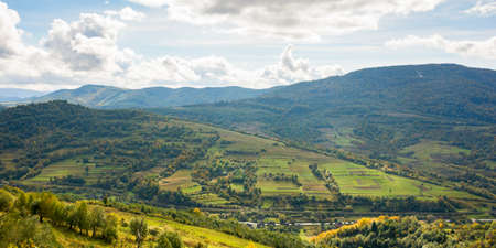 carpathian countryside landscape in early autumn. beautiful mountain landscape in dappled light. warm sunny day with clouds on the sky Stock Photo