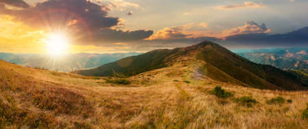 mountain landscape in early autumn at sunset. colorful scenery with peak and grassy hills in evening light. ridge in the distance beneath a cloudy sky. travel destination concept Stock Photo