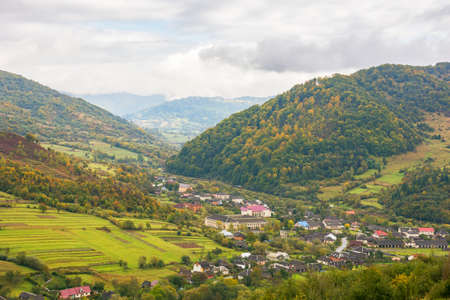 rural landscape in mountains. cloudy autumn weather. village in the distant valley