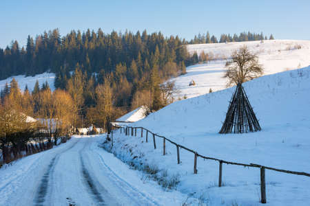road through village in mountains. beautiful winter scenery in afternoon. rural landscape among forested hills covered in snow Stock Photo
