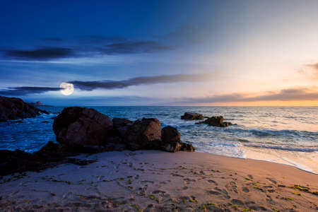 day and night time change concept above huge stones on the sandy beach at twilight. wonderful velvet season vacation. clouds on the blue sky with sun and moon above horizon. waves washing the shore Stock Photo