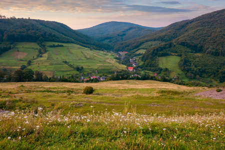 mountainous countryside landscape at dawn. pastures and rural fields near the forest on the hills. beautiful early autumn nature scenery with clouds on the sky in morning light