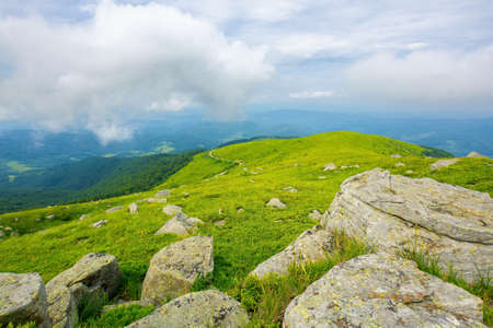 view from runa mountain. huge stones on the grassy slopes. summer landscape of carpathian mountains. bieszczady and vihorlat ridge in the distance beneath a sky low clouds