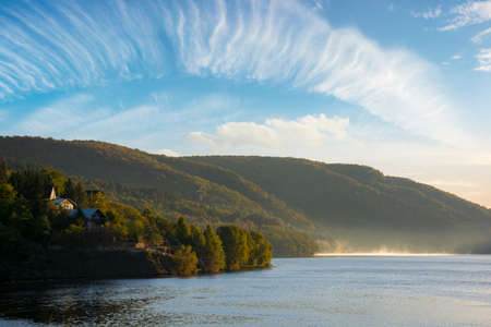 morning landscape of mountain lake at sunrise. beautiful autumnal countryside scenery with fog on the water in the distance. cold somes water reserve of cluj country, romania