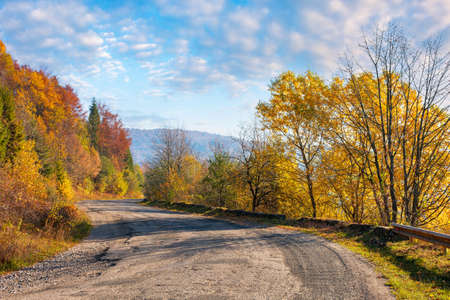 old mountain road in morning light. trees in colorful foliage along the serpentine. explore countryside concept Stock Photo