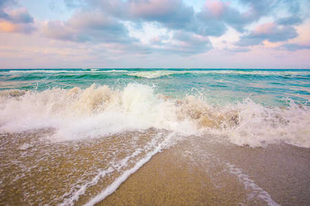 evening landscape at the sea. beautiful nature scenery. summer vacation concept. dramatic sky above the horizon. waves run on sandy beach