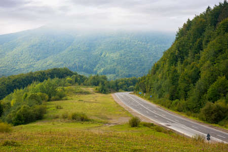 asphalt road through mountains on a cloudy day. wonderful rural landscape in early autumn