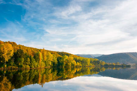 beautiful autumn landscape by the lake at sunset. trees in colorful foliage and forested apuseni mountains reflecting in the water surface. clouds on the sky in evening light
