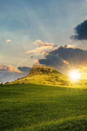 castle on the hill beneath a rainbow at sunset. composite fantasy landscape. grassy meadow in the foreground. rocky peaks of the ridge in the distant background in evening light