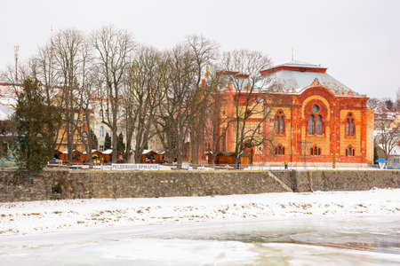 uzhgorod, ukraine - JAN 09, 2017: winter holidays in old town. embankment in snow and river uzh covered with ice. red building of old synagogue