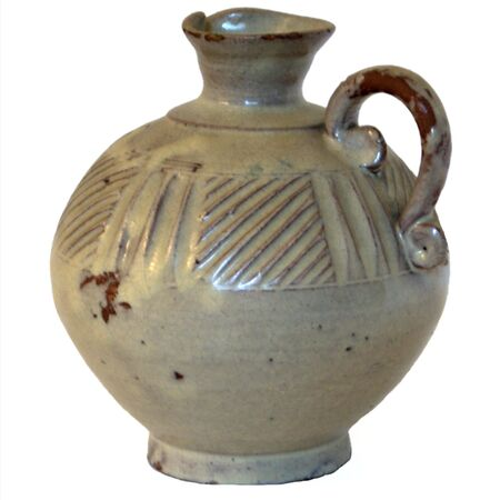 Isolated primitive antique majolica glazed pitcher on white background