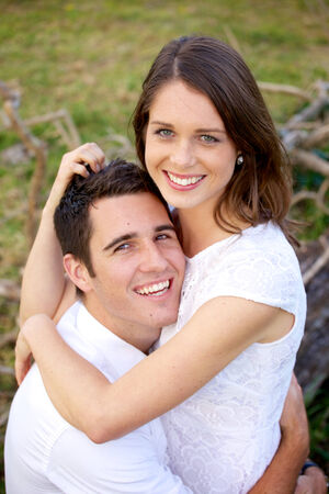 intimately: a young couple in white, on a green background, hugging intimately Stock Photo