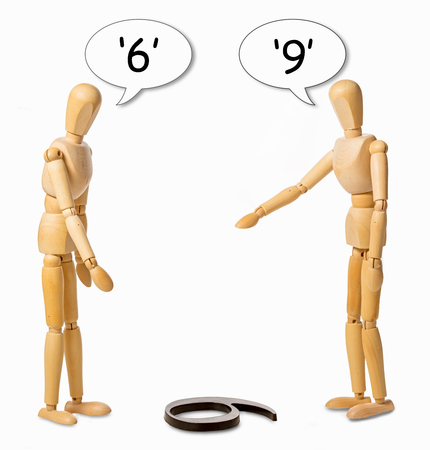 two mannikins arguing whether a number on the floor is a 6 or a 9 Stockfoto